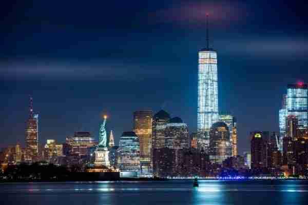 Statua della Libertà di notte con sfondo dell\'One World Trade Center